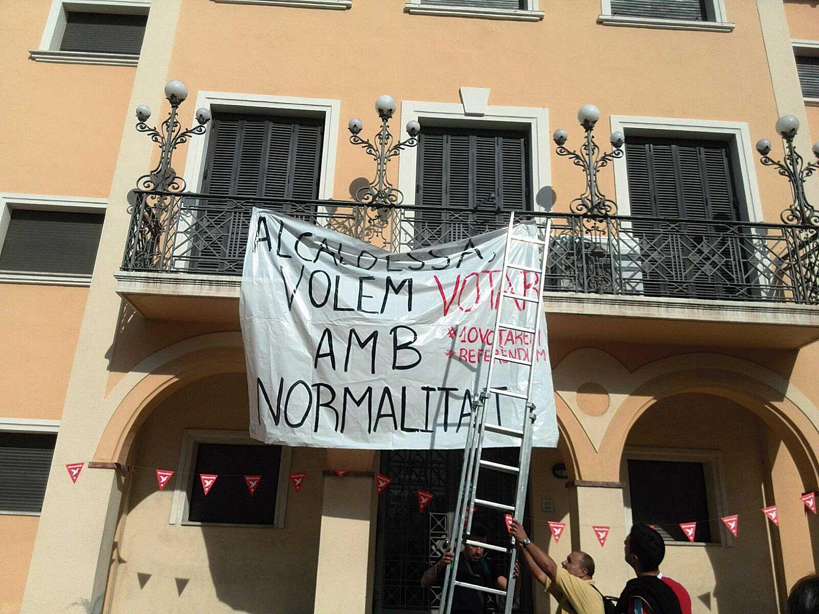 Desplegament d'una pancarta a la façana de la Casa de la Vila dels Monjos, reclamant votar en locals municipals.