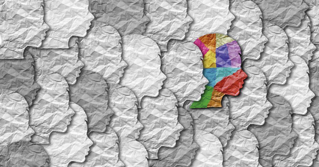 Silueta de cares de color gris i al centre, una de colors