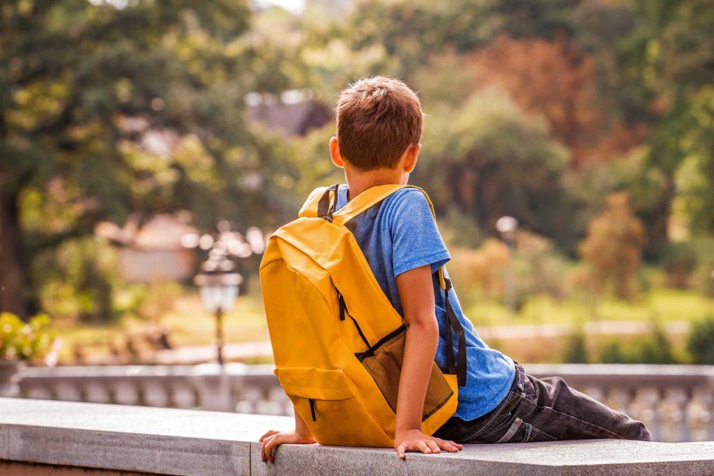 Un nen amb motxilla, sol i mirant l'horitzó