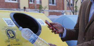 Imatge d'un contenidor groc amb una persona escanejant el codi QR abans de llençar una ampolla de plàstic
